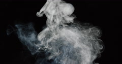 Smoke brifts upward from unseeen flame source, against black background Stock Footage