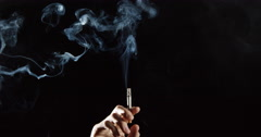 Elegant smoke rises from cigarette in hand, slow motion against black background Stock Footage
