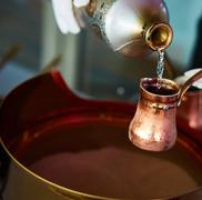 Preparation of Turkish coffee in the cezve in the sand at cafe bar Stock Photos