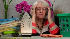 Elderly woman with headaches near ironing board Stock Footage
