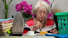 Elderly woman eating cake and drinking coffee near ironing board Stock Footage