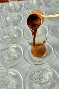 Pouring turkish coffee into traditional embossed cup - stock photo