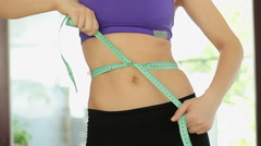 Slim woman measuring her waist by measure tape after a diet, close up HD Stock Footage