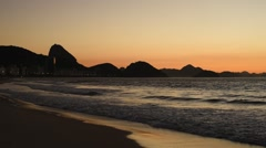 Copacabana beach by sunrise with the Sugarloaf Mountain in the horizon - stock footage