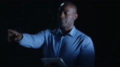4K Man using computer tablet & interactive touch screen on black background Stock Footage