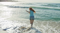 Young woman with long red hair in shorts pants play with waves running, feeling Stock Footage