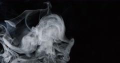 Billows of white turbulent smoke rise through frame against black background Stock Footage