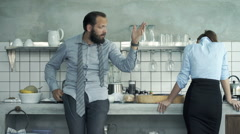 Business couple fighting, arguing in kitchen at home, businessman leaving  Stock Footage