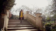 Girl downing the stairs in the Monceau parc in Paris Stock Footage