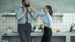 Business couple talking in kitchen, man tying necktie,woman drinking coffee Stock Footage