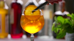 Tongs putting orange into cocktail. Stock Footage