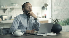 Bored, young businessman sitting by table in kitchen at home Stock Footage