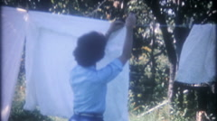 3355 young woman hangs laundry on backyard clothesline - vintage film home movie Stock Footage