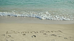 Dominicana drawn in the sea sand. rinse with sea water Stock Footage