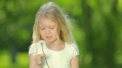 Little curly girl blowing dandelion. Stock Footage