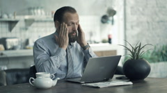 Young businessman having head pain during work on laptop by table at home  Stock Footage