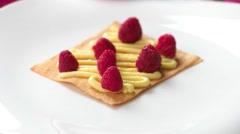 Hand puts shortcake on raspberries. Stock Footage