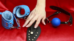 Leather accessories sex. female hand takes sex toy. mask, handcuffs and a gag Stock Footage