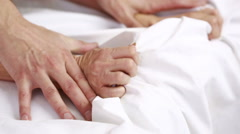 Hands of a couple in bed. Stock Footage