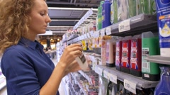 Young Woman Choosing Shampoo at Supermarket Stock Footage