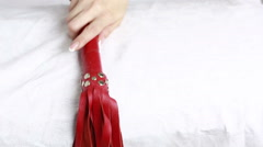 Girl takes a red leather whip. sex toys. Stock Footage