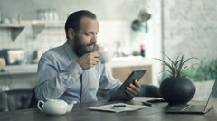 Businessman reading news on tablet and drinking coffee by table in kitchen Stock Footage