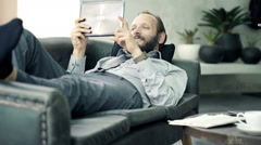 Young businessman watching movie on tablet lying on sofa at home Stock Footage