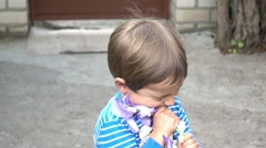 Child destroys iris flower playing Stock Footage