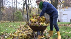 Tired woman load leaves to barrow and carry in house backyard. Handheld. 4K Stock Footage