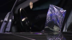 Police Officer gathers evidence, bag of collected items on the hood. Stock Footage