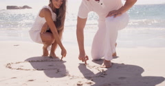 Couple writing on the sand Stock Footage