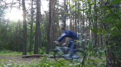 Bikers passing by the camera in a woods. Men spending her weekend outdoors. - stock footage