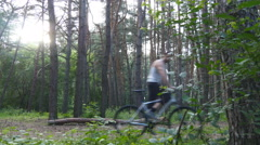 Two bikers riding a bike on pathway in forest. Stock Footage