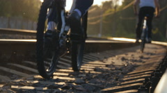 Two male friends riding bicycles on the rail track in sunset. Rear back view Stock Footage