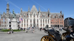 Provincial Court and horse-drawn carriages at Market square in Bruges, Belgium Stock Footage