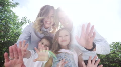 Happy family having fun outdoors in the park. Waving to camera. Slow motion - stock footage