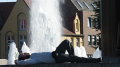 Tourist sleeping next to fountain at the square Het Zand in Bruges, Belgium Stock Footage