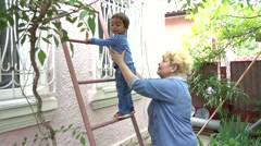 Grandmother takes her grandchild off the ladder - stock footage