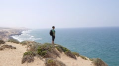 Man on top of sea mountain, looks into the distance. Conceptual design - stock footage