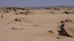 Young woman walking on beautiful inspirational desert dunes on sunny summer day - stock footage
