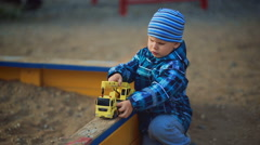 child playing in the sandbox with toy - stock footage