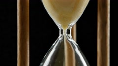 Hourglass is ticking. Yellow sand. Black. Close up - stock footage