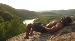 African american bodybuilder doing press ups on the rock in mountains. Green Stock Footage