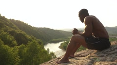 Side view of black african american man bodybuilder sitting on the rock and Stock Footage