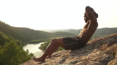 African american bodybuilder with naked torso doing press ups on the rock in Stock Footage