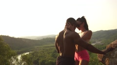Sexy fit mixed race couple with perfect bodies in sportswear posing on the rocky Stock Footage