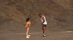 Young mixed race couple doing exercise outdoor on the stoned beach. Sexy Stock Footage