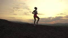 Silhouette of fit woman runner with perfect muscular body jogging outdoor on Stock Footage