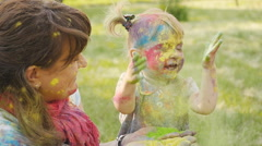 Family playing in the park. Family painted in the colors of Holi Festival - stock footage