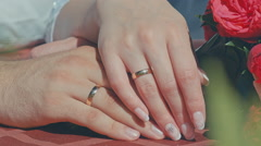 2 hands with wedding rings and bouquet on the table Stock Footage